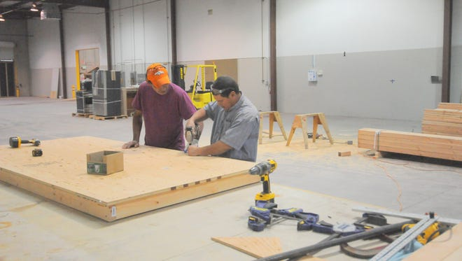 Humberto Elisondo, left, and Reynaldo Nunez of Peterson Products build a table on Oct. 28 as they help prepare the plant's new Dayton facility to begin production.