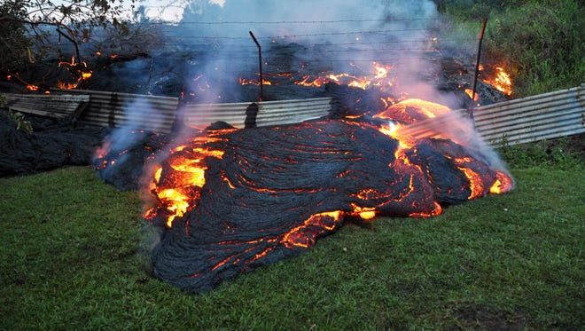 Lava that has pushed through a fence marking a property boundary above the town of Pahoa on the Big Island of Hawaii, Tuesday.