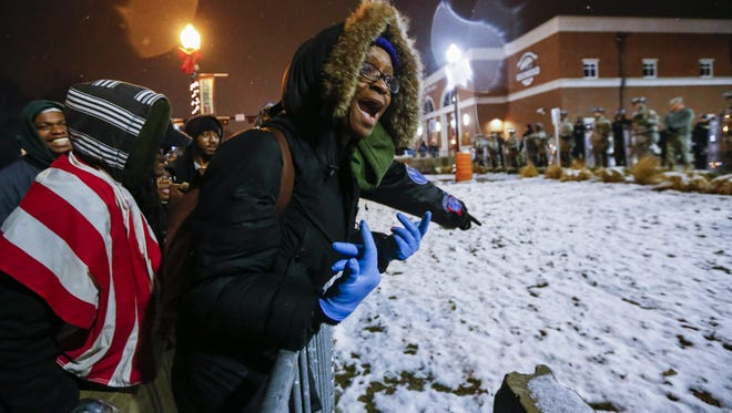 Protesters plead with members of the Missouri National Guard to abandon their positions in front of police headquarters as snow falls in Ferguson.