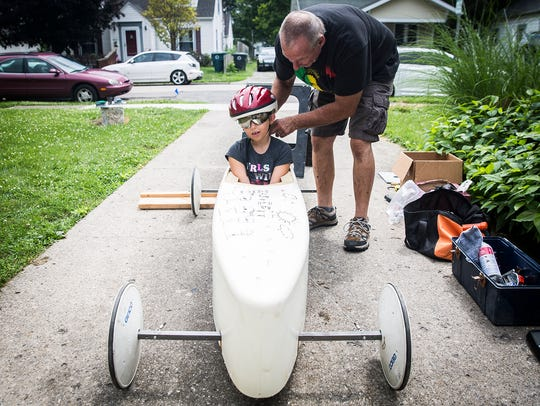 Kaylee Wallace fine tunes her soap box derby racer with her father and uncle at their Muncie home. The Wallace's have raced in the soap box derby for four generations.