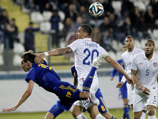 Ukraine's Denys Garmash, left, jumps for the ball with Geoff Cameron of the U.S. during an international friendly match at Antonis Papadopoulos stadium in southern city of Larnaca, Cyprus, Wednesday, March 5.
