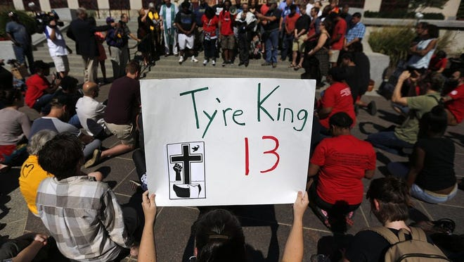 """About 150 people gather during a rally in response to the fatal police shooting of 13-year-old Tyre King at City Hall on Monday, September 19, 2016. Here most of the group take a knee when asked by organizers to """"take a knee for Tyre."""""""