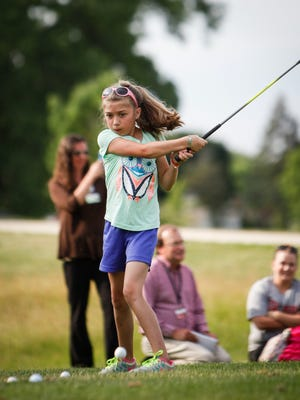 Olivia Polo, 8, of Holt practices her golf swing at First Tee Sycamore Driving Range in Lansing on Monday. She is one of about 10 young patients at Sparrow Pediatric Rehab who will participate in a golf outing in the fall.  Olivia had three open-heart surgeries before she was three, she suffered from a stroke at four due to hypoplastic left heart syndrome and had her fourth heart surgery shortly thereafter.   The purpose of the event is for the kids to participate in events outside of Sparrow Rehab and do things that typical kids do.