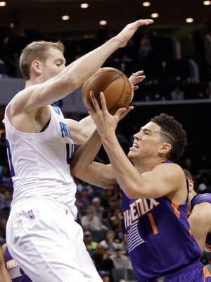 Phoenix Suns' Devin Booker, right, drives against Charlotte Hornets' Cody Zeller, left, in the first half of an NBA basketball game in Charlotte, N.C., Sunday, March 26, 2017.