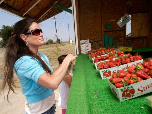 Kim Felsted, left, can't wait to purchase fresh strawberries at Caldwell Avenue and Ben Maddox Way in Visalia. Also pictured
