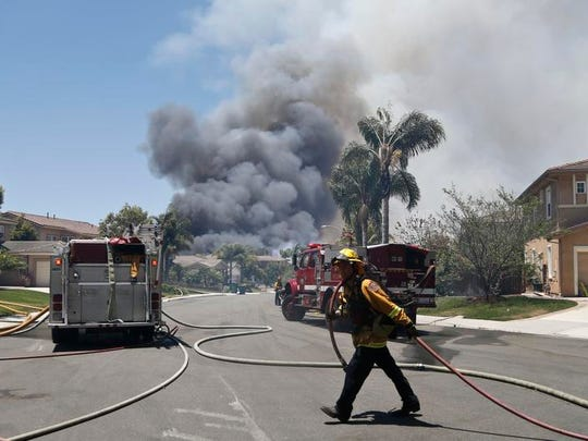 A fireman drags a hose as smoke rises from a nearby wildfire Wednesday, May 14, 2014, in Carlsbad, Calif. Carlsbad city officials said mandatory evacuations were in progress Wednesday, and more than 11,000 notices were sent to homes and businesses.  (AP Photo)