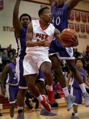 PikeÕs Justin Thomas (12) drives by Ben DavisÕ Naeem Freeman (40),right, and LeShaun Minor (50) in the second half of their Boys Marion County quarterfinal game Wednesday, Jan 13, 2016, evening at Pike High School. Pike defeated Ben Davis 68-49.