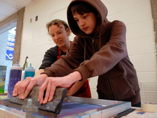 Rachel Mauser, left, helps Aidan Roberts, 13, make a screen print at the Louisville TimeBank's first annual Share Fest at Jefferson Community and Technical College.  March 29, 2015