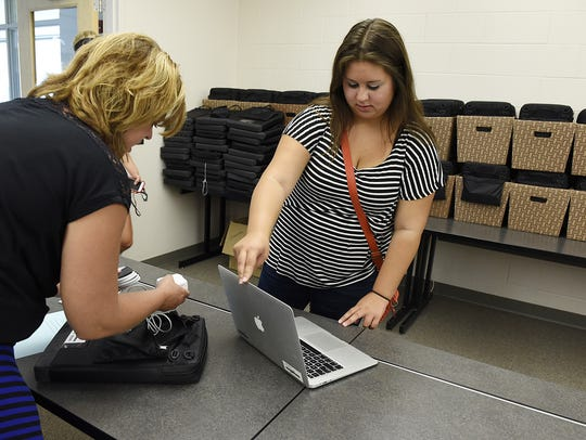 A high school student in Minnesota examines a new Macbook.