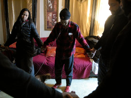Sojourner, Althea Tangco (cq), left, holds June Alexander's hand in prayer, center, at Alexander's house in the Shelby Park neighborhood. The Sojourn Church does a weekly community outreach where the visit members of the neighborhood.  Alexander is fighting throat cancer and chronic obstructive pulmonary disease (COPD).     Feb. 15, 2016