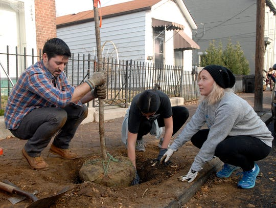 Robert Glasnovic, left, holds a tree straight while