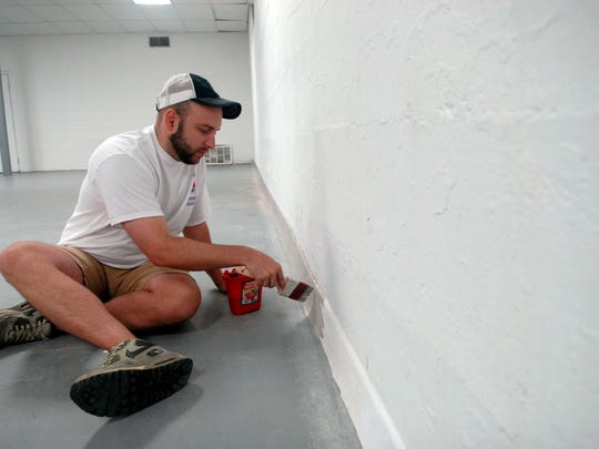 Tyler Dee works on the baseboard trim at the Mackin Community Center on 26th Street.  The paint job was part of the National Painting League's volunteer project through Sherwin Williams.  May 20, 2016