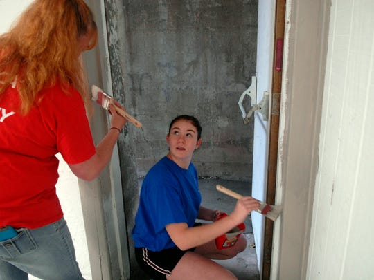 Sherry Burckhardt, left, and her daughter, Katie Ables, right, paint trim in the basement of the Mackin Community Center on 26th Street.  The room will be used for a summer school program.  May 20, 2016