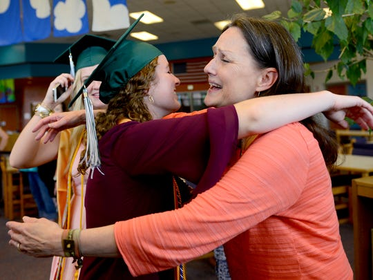 "Librarian Sandra Nagy hugs senior Lydia Kugler after reading ""Oh, the Places You'll Go,"" by Dr. Seuss to Williamston High School seniors Friday at the elementary school library after they walked the hall and gave high-fives to students  on one of their last days in the district before graduation."