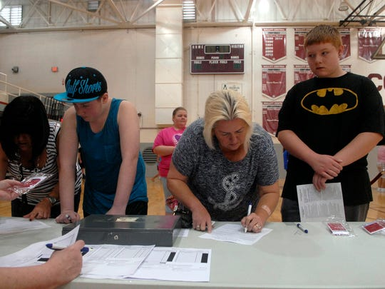 Cathy Brooks, second to right, signs up her son, Jordan, 14, for a new laptop.  To better prepare students for an increasingly digital world, Bullitt County Public Schools will this year provide laptops to every high school freshman, sophomore and junior.
