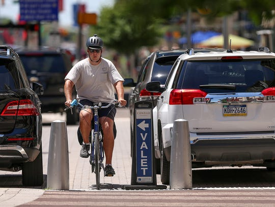 A bicyclist weaves in between cars in the valet parking