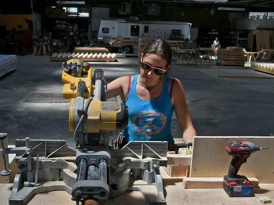 "In a vacant warehouse east of downtown Reno, volunteer Rachel ""Chipper"" McKay cuts wood parts for ""the man,"" the wooden effigy that is traditionally burned on the Saturday night at the Burning Man event."