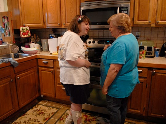Stephanie Rudy, 32, helps her mother, Martha make a spaghetti dinner in their Bashford Manor home.  Stephanie had a stroke at 10-months-old and as a result needs special care.