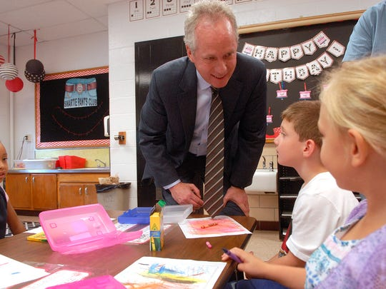 Mayor Greg Fischer introduces himself to a kindergarten student on the first day of school at Wilder Elementary School Wednesday morning.  August 16, 2017
