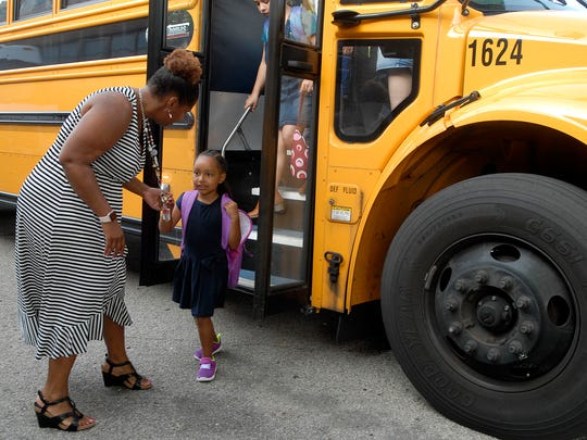 Assistant Principal Wallis Owens helps students off the bus on the first day of school at Wilder Elementary School Wednesday morning.  August 16, 2017