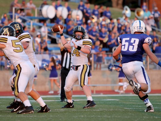 Henrietta's Zack West looks to pass to a receiver in the season opener against Windthorst Friday, Sept. 1, 2017, in Windthorst.