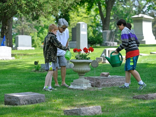 Aden Johnson, 9, waters flowers with his grandma, Naomi Massa, and his sister, Katie Mehrezadeh, 11, at Woodlawn Cemetery in Sioux Falls on Friday.