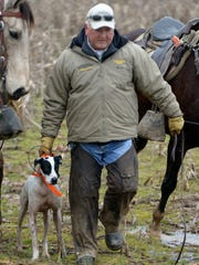 Brad Kennedy walks his dog, Mega Blackhawk's Progeny, to an open field after one of its two finds during the 117th Annual National Field Trial Champion Association's National Championship for Bird Dogs on Wednesday morning