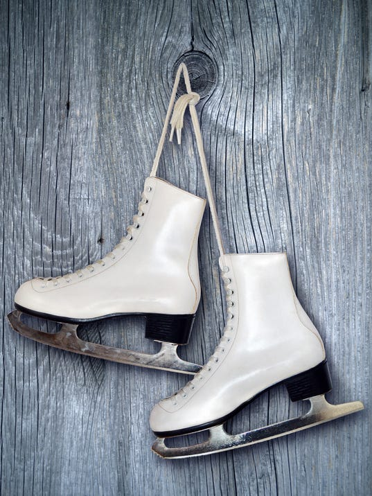 Pair of White Ice Skates on wooden  backround