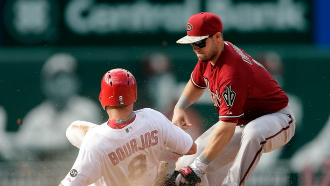 Arizona Diamondbacks second baseman Chris Owings, right, tags St. Louis Cardinals' Peter Bourjos out at second on a steal attempt during the eighth inning of a baseball game Monday, May 25, 2015, in St. Louis.