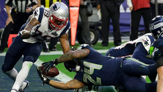Seattle Seahawks running back Marshawn Lynch (24) dives into the end zone for a touchdown in front of New England Patriots cornerback Brandon Browner (39) during the first half of NFL Super Bowl XLIX football game Sunday, Feb. 1, 2015, in Glendale, Ariz.