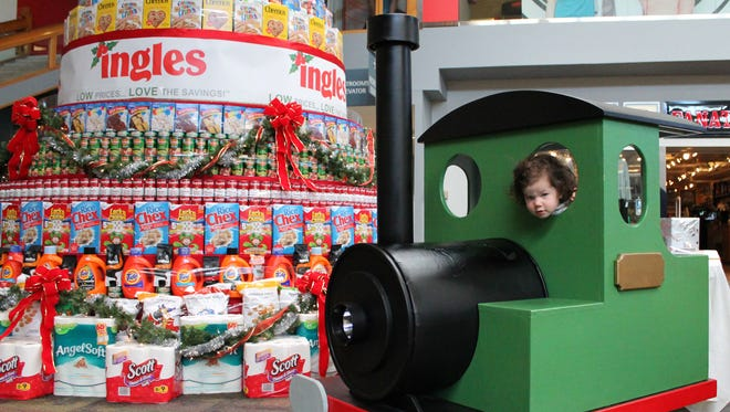 A child plays near the  Ingles Giving Tree at the Asheville Mall on Monday. The Giving Tree is a 10-ton construction of non-perishable food items donated by Ingles Markets and decorated by staff and volunteers at MANNA FoodBank.
