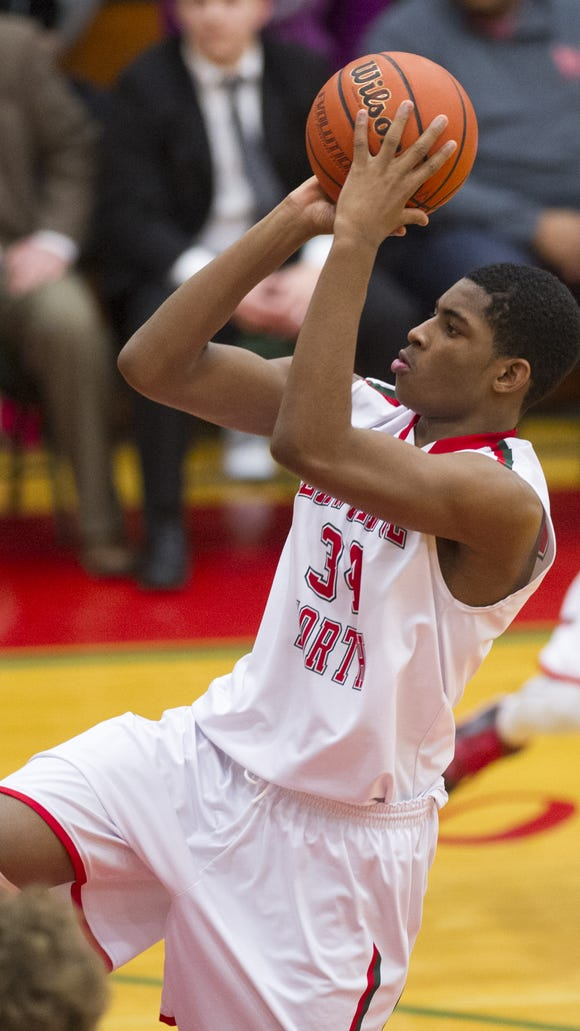 Lawrence North High School freshman Kevin Easley, Jr. (34) puts up a shot during the second half of action. Lawrence North High School hosted North Central High School in a first-round game of the 2015 Marion County Boys Basketball Tournament, Tuesday, Jan. 13, 2015. Lawrence North defeated North Central 61-57 to advance in the tournament.