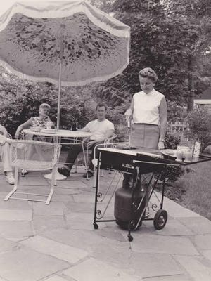 A woman demonstrates using a LazyMan portable grill in this vintage advertisement.