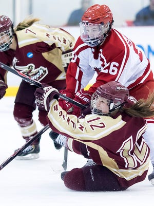 Norwich's Vanessa Champagne fires a shot despite being dropped to the ice by Plattsburgh's Melissa Sheeran during Friday's NCAA Division III women's hockey game at the Ronald B. Stafford Arena in Plattsburgh, N.Y.