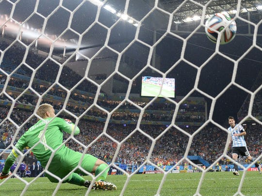 Netherlands goalkeeper Jasper Cillessen fails to stop a shot from Argentina's Lionel Messi during a penalty shootout following extra time in the World Cup semifinal Wednesday.