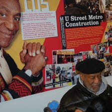 Bill Cosby in front of the poster that details his connection with Ben's Chili Bowl