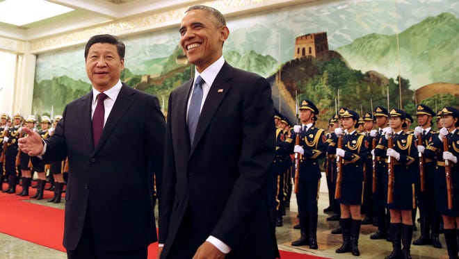 President Obama smiles as he walks with Chinese President Xi Jinping during a welcome ceremony at the Great Hall of the People in Beijing on Nov. 12.
