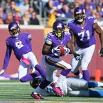 Vikings running back Jerick McKinnon carries the ball while quarterback Teddy Bridgewater (5) gets tackled by Jason Jones of the Detroit Lions at TCF Bank Stadium in Minneapolis.