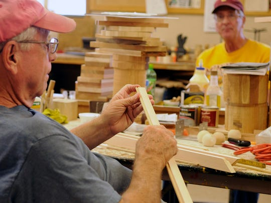 """Mel Strack, left, works on building """"little free libraries"""" for St. Cloud neighborhoods Monday, Aug. 15, 2016, in the wood shop at Whitney Senior Center. Also pictured is Dale Gabrielson."""