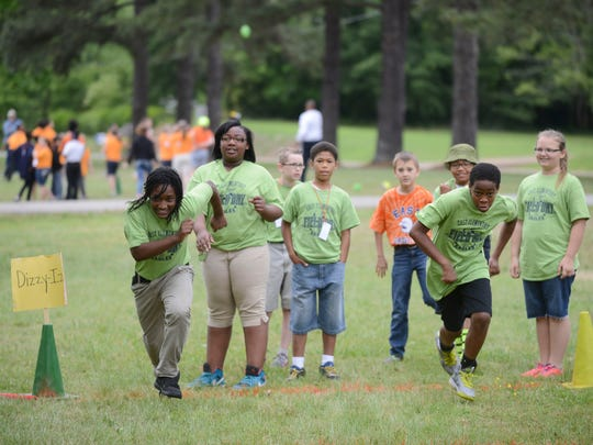 Kids run during a game of Dizzy Bat during field day Thursday at East Elementary School.
