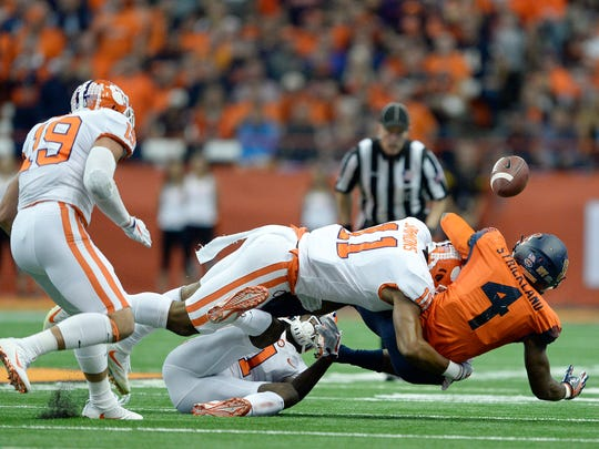 Syracuse running back Dontae Strickland (4) fumbles the ball after being hit by Clemson safety Isaiah Simmons (11) during the first half of an NCAA college football game, Friday, Oct. 13, 2017, in Syracuse, N.Y. The ball was picked up by Clemson safety Tanner Muse (19) and returned for a touchdown. (AP Photo/Adrian Kraus)