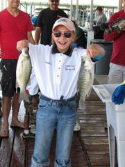 Donald R. Kemp Youth Hunting Club member Madison Estrada, holds up two fish during the  DRK Fishing Classic at Elephant Butte Lake.