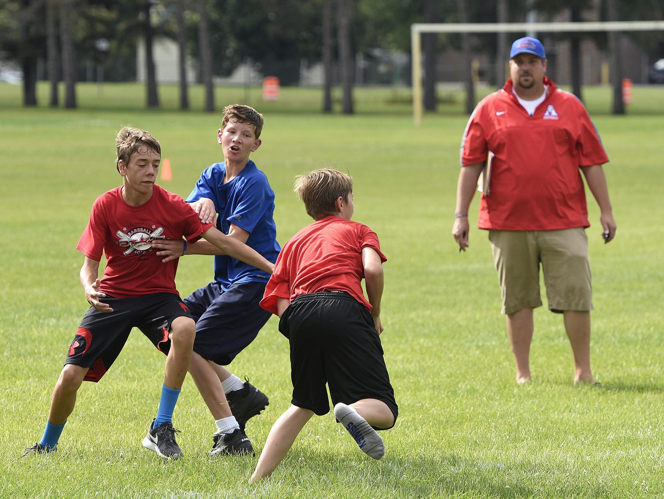 Apollo High School head football coach Justin Skaalerud watches as a touch football play unfolds Friday during the last youth camp session at the high school in St. Cloud.