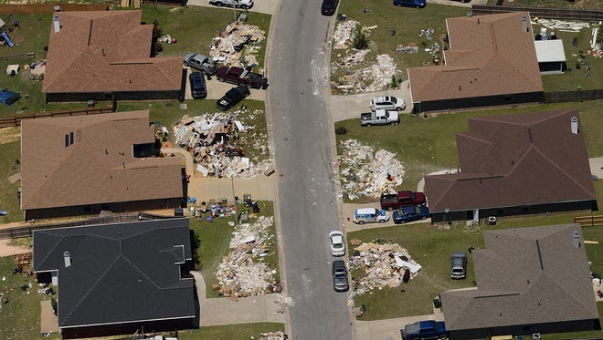 FILE PHOTO Cantonment area residents were heavily hit by 2014's flooding, as seen from the Bristol Park neighborhood. Most of the houses in the area have large piles of debris stacked along the streets.