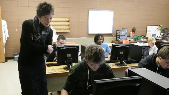 Kohler Credit Union's Laura Gabrielse observes a student working on Bonzai, a personal finance program, at Plymouth High School.