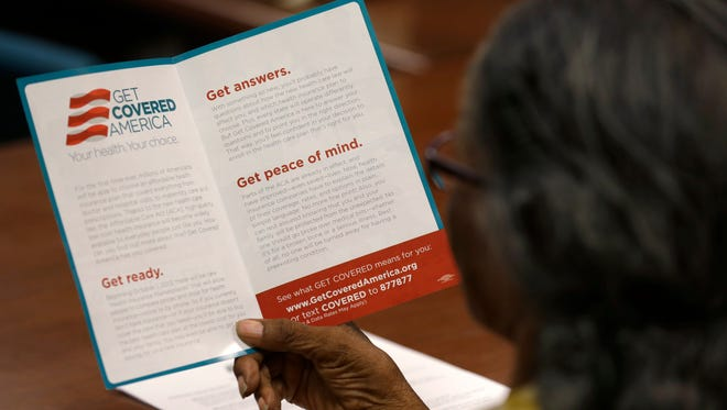 Eufaula Frazier, a volunteer with Enroll America, a private, non-profit organization running a grassroots campaign to encourage people to sign up for health care offered by the Affordable Care Act, reads over a pamphlet before making calls to inform people of their health care options.