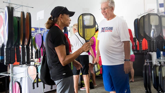 """Carole Patterson, a volunteer with the U.S. Open and Naples local, speaks with Ken McEvoy, a sales representative for Paddletek, while perusing for a new pickleball paddle at East Naples Community Park Thursday, April 27, 2017. """"It has tremendous addictive qualities,"""" said McEvoy. """"I've never seen a sport where people start it and play it almost daily."""""""