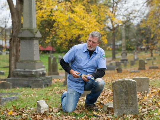 Mark Parrot repairs a broken memorial at Old Gray Cemetery on Saturday, November 18, 2017. Parrot is a caretaker at Mountain Home National Cemetery in Johnson City and heard about Old Gray Cemetery's problem with damaged headstones and decided to organize a group of fellow employees to spend a Saturday volunteering their expertise to repair many of the cemetery's broken memorials.