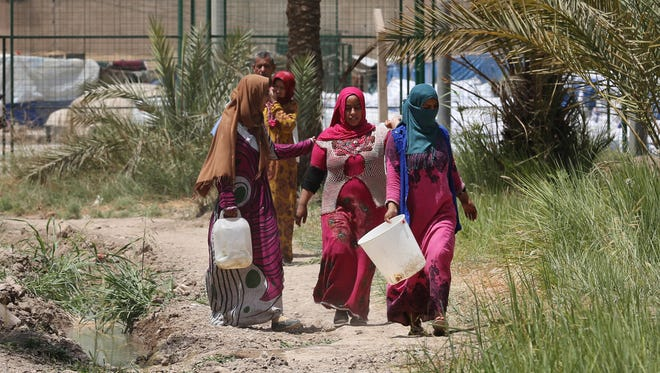 Iraqis displaced by conflict walk on a path on their way to collect water at al-Takia refugee camp in Baghdad on July 30, 2015. Scorching temperatures are normal this time of year, but an unprecedented heat wave prompted Iraqi authorities to declare a mandatory four-day holiday.