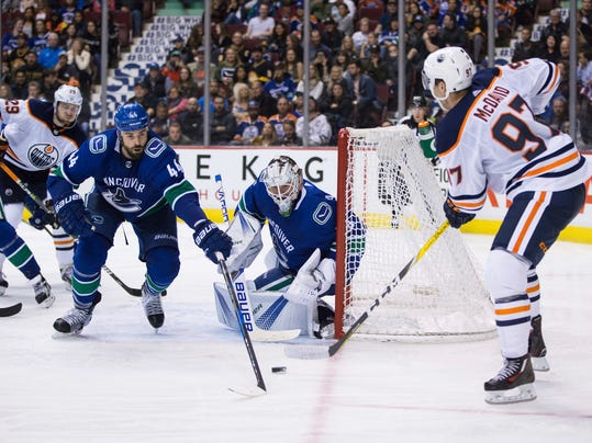 Edmonton Oilers' Connor McDavid, right, is stopped by Vancouver Canucks' goalie Jacob Markstrom, of Sweden, as Erik Gudbranson (44) defends during the third period of a preseason NHL hockey game in Vancouver, British Columbia, Saturday, Sept. 30, 2017. (Darryl Dyck/The Canadian Press via AP)